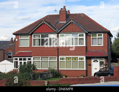 Typical 1930s English brick built semi-detached house with triangles over bedrooms, front garden shared chimney - Stock Photo
