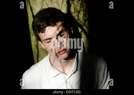 Young man with shadow of tree branches in the face - Stock Photo