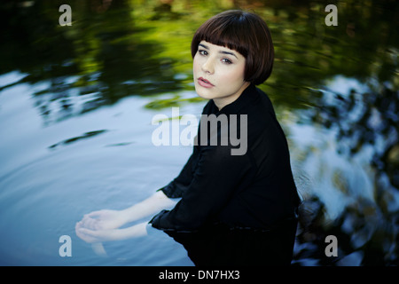 Young woman sitting in water, portrait - Stockfoto