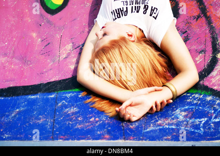 Woman lying on floor with graffiti - Stock Photo