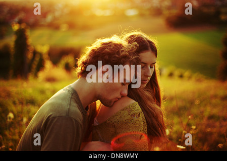 Young couple in love embracing on a meadow - Stock Photo