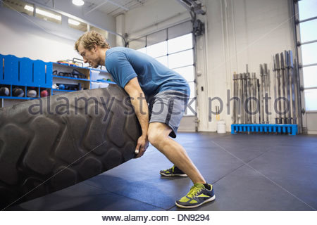 Man doing tire-flip exercise in Crossfit gym - Stock Photo