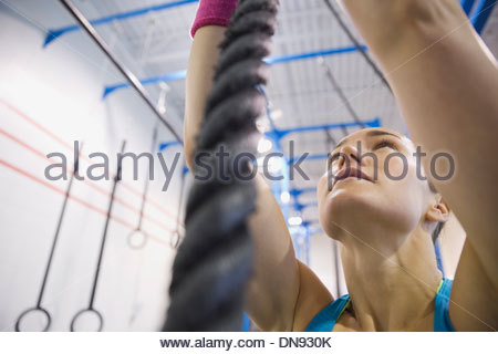 Woman climbing rope in Crossfit gym - Stock Photo