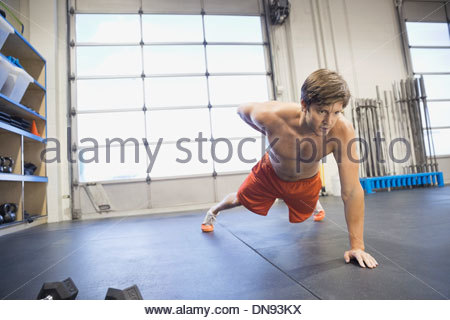 Man doing one arm push-ups in gym - Stock Photo