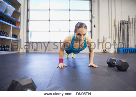 Determined woman performing push-ups in gym - Stock Photo