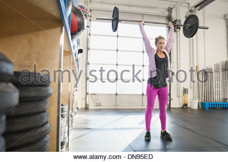 Woman practicing clean and jerks in Crossfit gym - Stock Photo