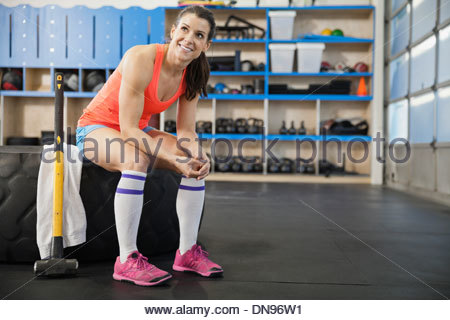 Woman sitting on tire in Crossfit gym - Stock Photo