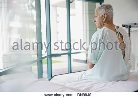 Thoughtful senior patient sitting on hospital bed - Stock Photo