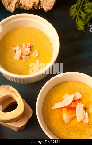 Yellow custard in white souffle dishes overhead - Stock Photo