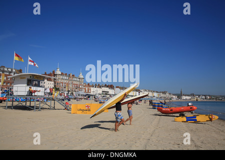 Two canoeists Lifeguard hut with lifeguard on beach in front of the Bay Royal Hotel The Esplanade, Weymouth, Dorset, - Stock Photo