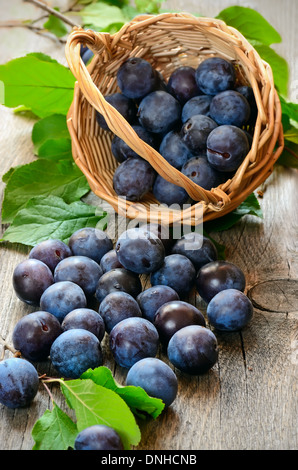 Ripe plums on the wooden table - Stock Photo