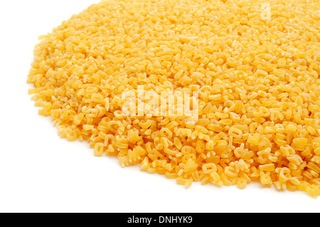 a pile of uncooked alphabet pasta on a white background - Stock Photo