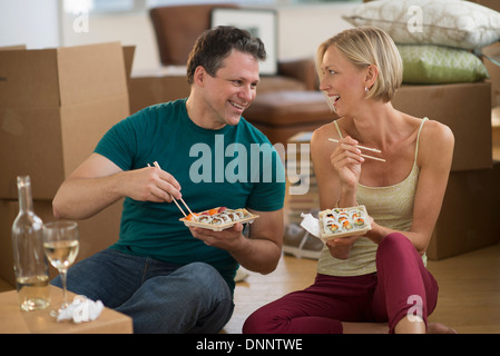 Couple eating sushi in new home - Stock Photo