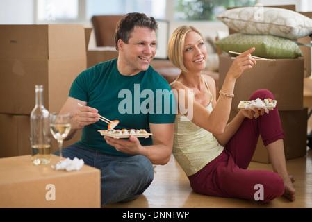 Paar Sushi-Essen im neuen Zuhause - Stockfoto