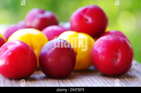 Ripe plums on wooden table on green background - Stock Photo