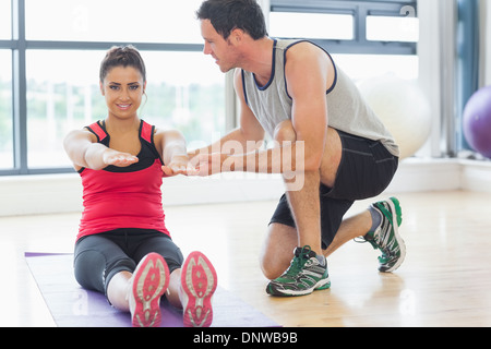 Male trainer assisting woman with pilate exercises in fitness studio - Stockfoto