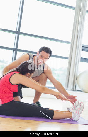 Trainer assisting woman with pilate exercises in fitness studio - Stockfoto