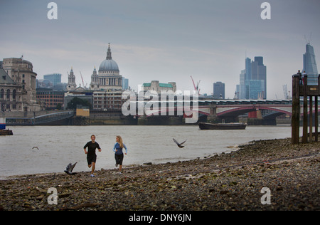 Gary Hicking, personal trainer in London, UK, jogging with a client along the Thames with the city of London as - Stock Photo