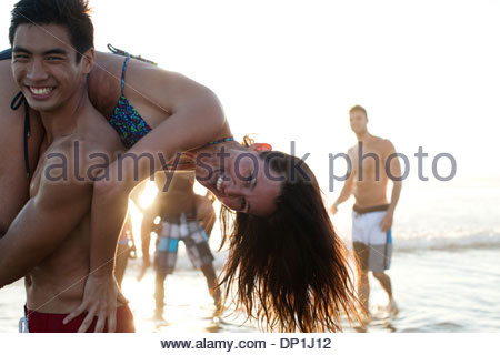 Friends playing in waves on beach - Stock Photo