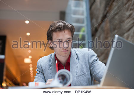 Businessman with laptop at table looking pensive - Stock Photo
