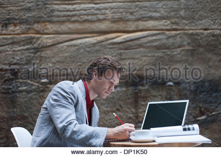 Businessman writing in notepad at table with laptop and coffee - Stock Photo