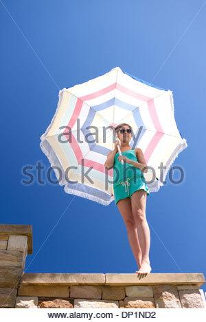 Woman in sunglasses holding beach umbrella - Stock Photo