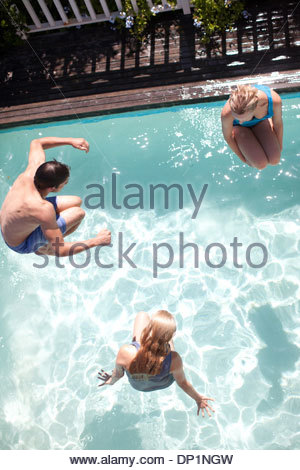 Friends jumping in swimming pool - Stock Photo