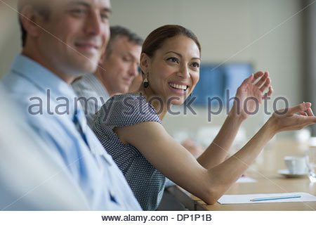 Smiling businesswoman in meeting in conference room - Stock Photo