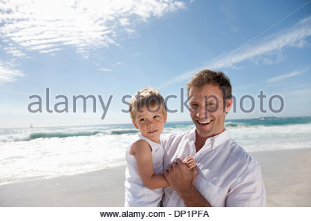 Father holding son on sunny beach - Stock Photo