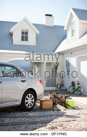 Picnic basket, fishing rod, flippers and bags outside car in driveway - Stock Photo