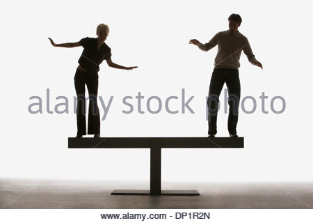 Two people balancing on top of a plank - Stock Photo