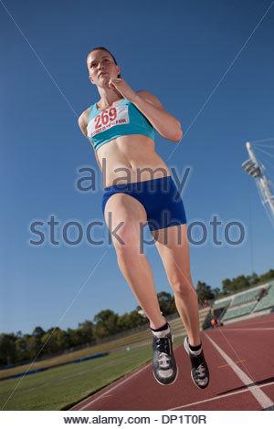 Woman running on track - Stock Photo