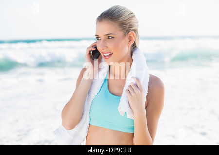Cheerful fit blonde in sportswear on the phone - Stock Photo
