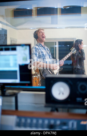 Young band playing in studio - Stock Photo