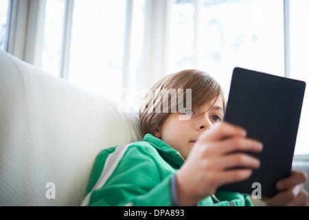 Boy on sofa using digital tablet - Stock Photo