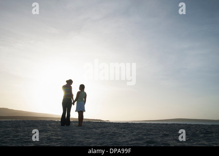 Mother and daughter holding hands on beach - Stock Photo
