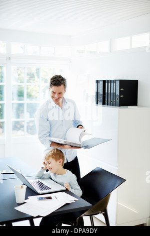 Boy using laptop and man looking at paperwork - Stock Photo