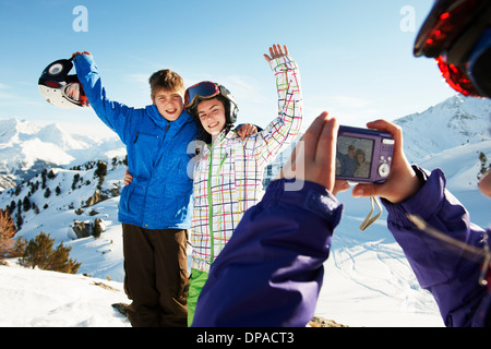 Girl photographing siblings, Les Arcs, Haute-Savoie, France - Stock Photo