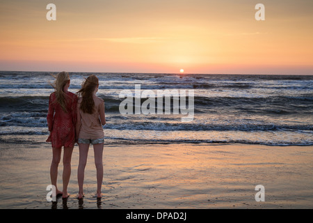 Mother and daughter looking at sunset - Stock Photo