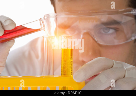 Close up of scientist pouring liquid into test tube - Stock Photo