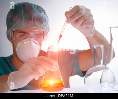 Scientist pouring liquid from pipette - Stock Photo
