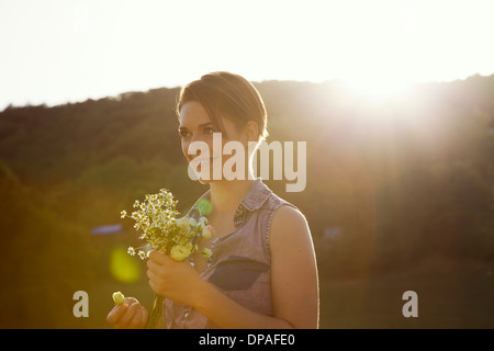 Young woman in meadow with bunch of wild flowers - Stock Photo