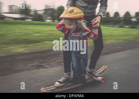 Mother and daughter riding on skateboard in park - Stock Photo