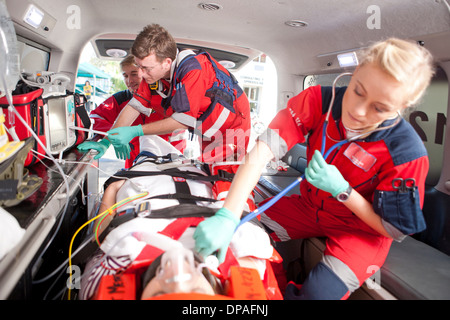 Paramedics using stethoscope on patient in ambulance - Stock Photo