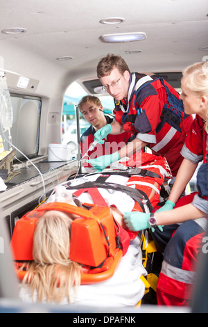 Paramedics with intravenous drip and patient in ambulance - Stock Photo