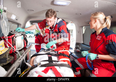 Paramedics checking patient in ambulance - Stock Photo