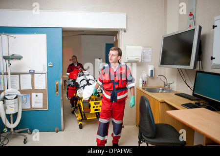 Paramedics moving patient to emergency room in hospital - Stock Photo