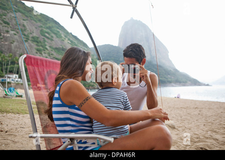 Man taking photograph of mother and son on chair, Rio de Janeiro, Brazil - Stock Photo