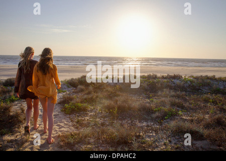 Mother and daughter walking towards beach - Stock Photo