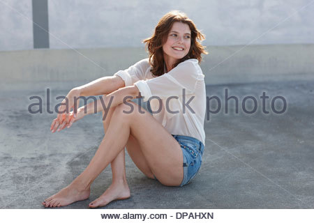 Portrait of young woman sitting on concrete floor - Stock Photo